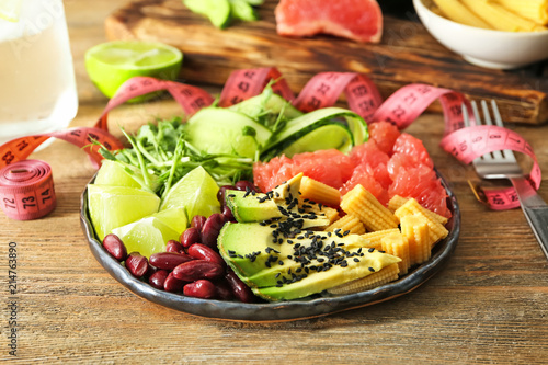 Recess Fitting Appetizer Plate with delicious fresh salad and measuring tape on table. Diet concept