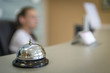 a silver bell of a hotel to meet guests against a blurry receptionist. an important accessory at the reception and a wonderful background.