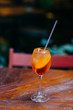 Shot of fresh summer cocktail with orange and ice in wine glass. Aperol spiritz cocktail in bar with no people. Blurred background. Drink for party