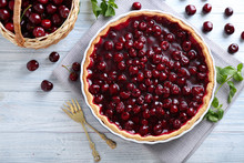 Tasty Homemade Pie And Basket With Ripe Cherries On White Wooden Table
