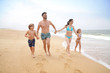 Cheerful family running on sandy beach