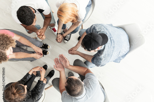 Obraz Top view on difficult youth talking with therapist while sitting in a circle during meeting - fototapety do salonu