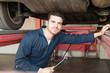 Handsome Mechanic Holding Spanner Under Car