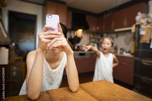 Valokuva スマートフォンで会話する母親と怒る娘