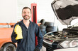 Smiling Mechanic With Motor Oil Can Standing In Garage