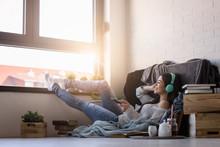 Beautiful Young Woman At Home Enjoys Listening Music Through Headphones