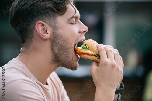 In de dag Kruidenierswinkel side view of man eating tasty burger with closed eyes
