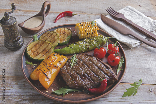 Photo Stands Grill / Barbecue beef steak with grilled vegetables on the plate