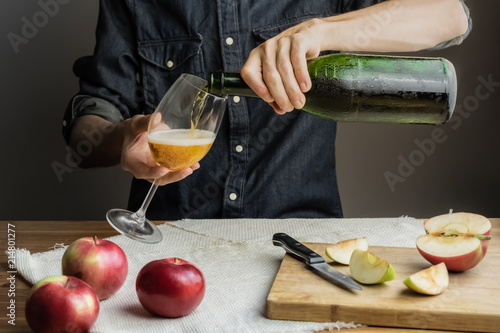 Obraz na płótnie Male hands pouring premium cidre in wine glass above rustic wood table