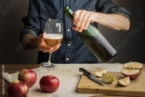 Tableau sur Toile Male hands pouring premium cidre in wine glass above rustic wood table