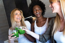 Pretty Young Women Toasting With Detox Green Juice And Smiling At Home.