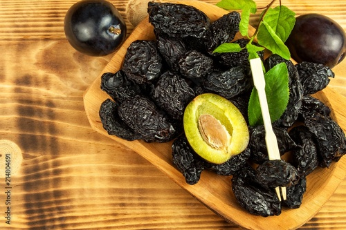 Prune, dried plums fruits on rustic wooden background. Dry plums in a wooden bowl. Healthy fruit.