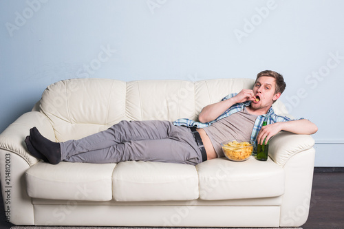 Man with beer and chips watching TV at home Wallpaper Mural