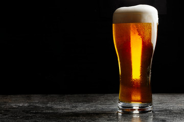 Čaša hladnog craft svijetlog piva na tamnoj pozadini ..