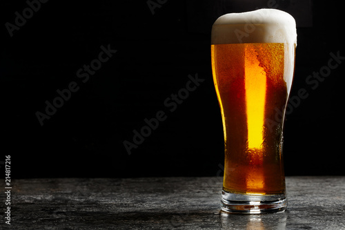Glass of cold craft light beer on dark background..