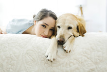 Woman Lying On Bed With Dog