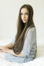 Portrait Of Teenage Girl Sitting On Bed
