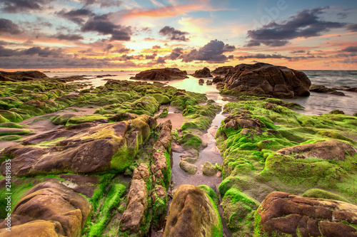 Foto op Aluminium Zalm view of beautiful sunset sky at unknown beach in Sabah, Malaysia. Natural coastal rocks covered by green moss on the ground. soft focus due to long expose.
