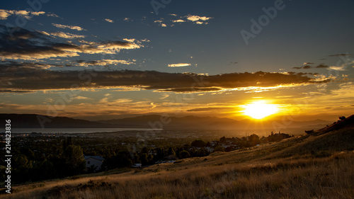 Sunset over a city in a valley with mountains and a large lake in the distance Canvas Print