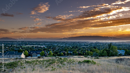 Fotografie, Obraz  Sunset over a city in a valley with mountains and a large lake in the distance