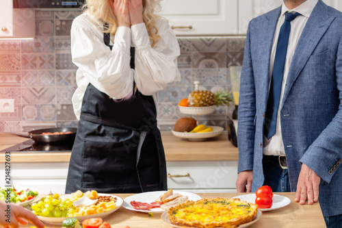 In de dag Assortiment Woman housewife meets the man of the guest next to the table with food