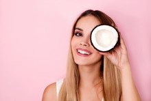 Happy Young Woman Holding Coconut Piece In Front Of Eye