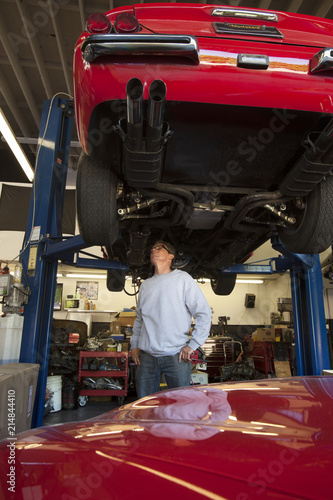 Owner of auto repair shop inspecting automobile elevated on a lift