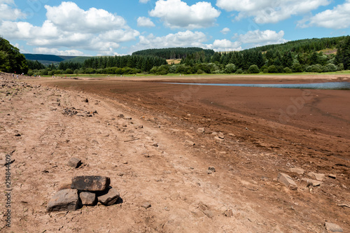 A dried up reservoir showing just dust and rocks during a summer heatwave (Llwyn Poster Mural XXL