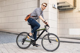 Fast vehicle. Smart handsome man riding a bike in the city while going to work in the office