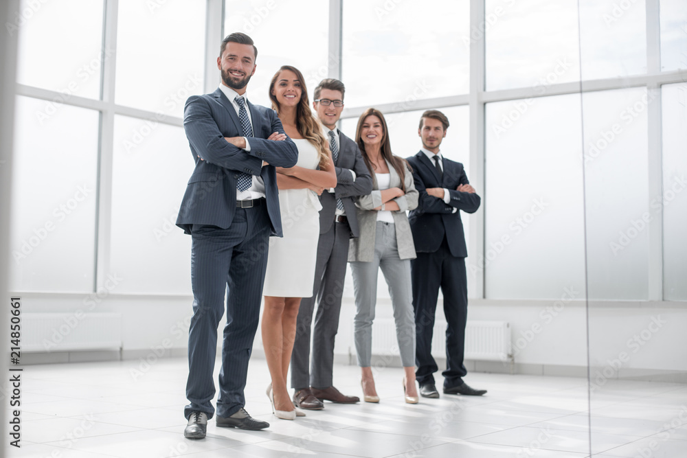 Fototapeta group of businessmen and businesswoman standing in an office with a large window