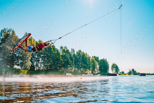 Fotografie, Obraz  Young man wakeboarding on a lake, making raley, frontroll and jumping the kickers and sliders