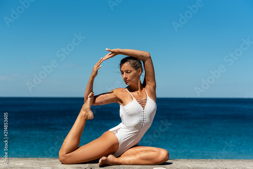 Poster  Attractive woman in her 40s, practicing yoga on sea side, doing One Legged King Pigeon Pose - Eka Pada Rajakapotasana,  in white swimsuit, with sea in the background