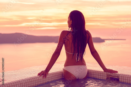 Luxury hotel swimming pool bikini model woman relaxing in jacuzzi spa with Mediterranean sea view at sunset. Girl coming out of water with healthy long hair, body care wellness concept.