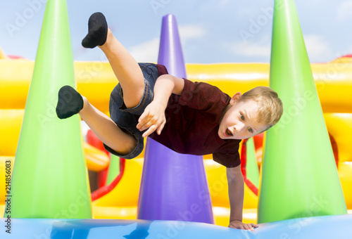 Fotografia  Child jumping on colorful playground trampoline