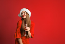 Young Beautiful Woman In Santa Hat With Glass Of Champagne On Color Background. Christmas Celebration