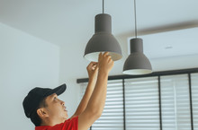 Hands Mechanic Changing With New LED Lamp Light Bulb,Power Saving Concept