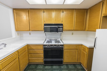 Old Condo Kitchen With Oak Cabinets, Tile Countertops, Gas Stove And Green Vinyl Flooring.  Unchanged Since 1988.