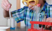 Experiments On Chemistry At Home. Boy Pours Blue Liquid From The Beaker Into The Tube With A Pipette.