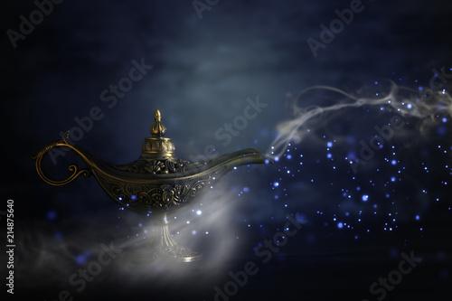 Obraz na plátně  Image of magical mysterious aladdin lamp with glitter sparkle smoke over black background