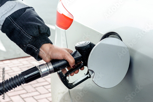Fotografie, Obraz  Woman pouring gasoline into the car. Hand close-up.