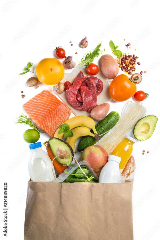 Fototapeta Grocery shopping concept. Balanced diet concept. Fresh foods with shopping bag on white background