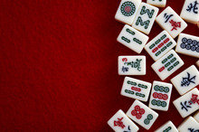 Traditional Chinese Games And Tile Based Game Concept With Mahjong Pieces Isolated On Red Background With Copy Space