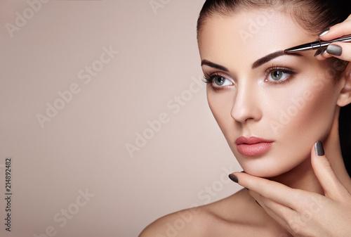 Fotografija Beautiful Brunette Woman Paints the Eyebrows