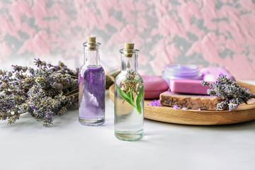 Obraz na płótnie Canvas Bottles of essential oil with lavender on table
