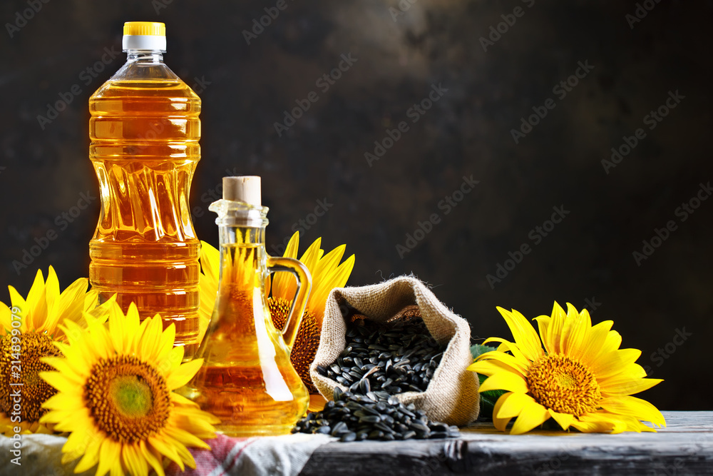 Fototapety, obrazy: Closeup photo of sunflowers and sunflower oil with seeds on on a wooden table. Bio and organic concept of the product.