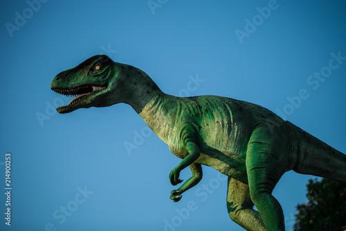 Model of Velociraptor roaring against blue sky Canvas Print