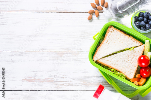Foto op Aluminium Assortiment Lunch box with sandwich, vegetables, water, nuts and berries.
