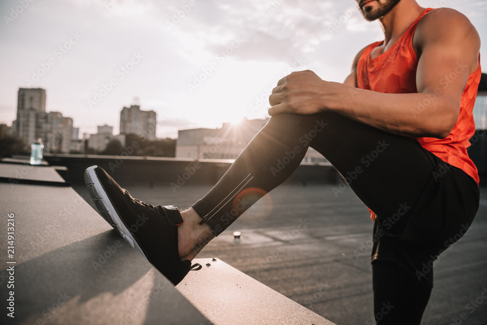 Fototapety, obrazy: cropped image of sportsman stretching legs on roof during sunset