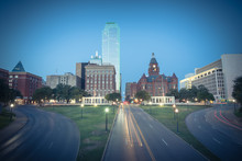 Vintage Tone Beautiful View Of Dallas Skyscrapers And Light Trail Traffic Over Dealey Plaza, JKF Assassination Site. Skyline And Transportation Cityscape At Blue Hour