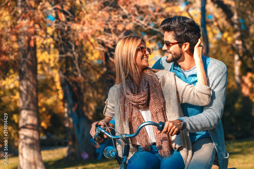 Happy young couple having fun riding a bicycle on sunny day in the park Wallpaper Mural